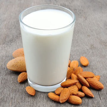 glass of almond milk and almonds
