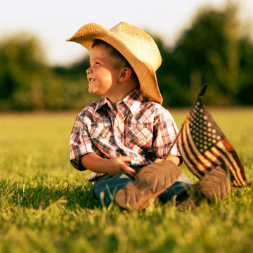 baby boy wearing a cowboy hat and holding an American flag