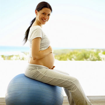 pregnant woman sitting on an exercise ball