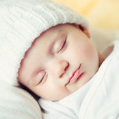 cut baby sleeping in a white hat
