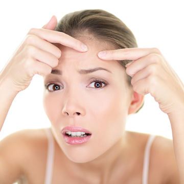 Woman with acne looking at pimple