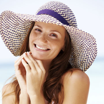 Woman with clear skin wearing a sun hat
