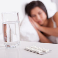 vitamins-with-water-woman-sleeping-in-background_700x700_shutterstock_121739785.jpg