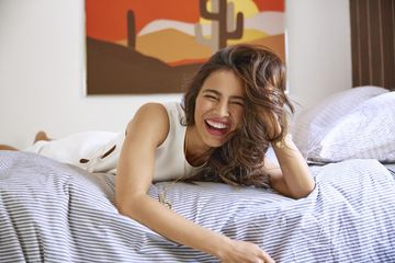 Mom in White Dress Laughing in Bed