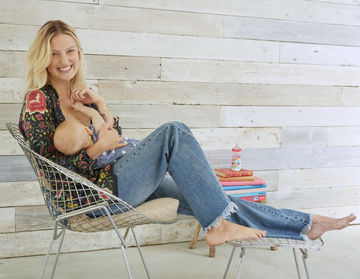 Happy Mother Breastfeeding Baby Sitting in Chair