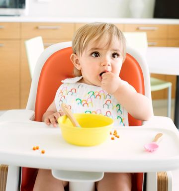 Baby Sitting In Highchair Eating Out Of Bowl