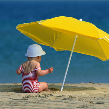 baby sitting under an umbrella