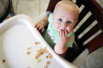 Baby feeding herself cheerios