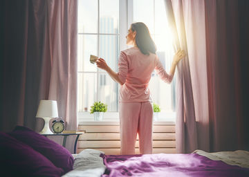Woman In Pajamas Made Bed Open Curtains Drinking Coffee