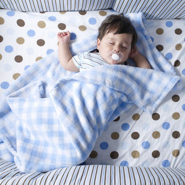 baby sleeping in crib with blankets -- SIDS Update