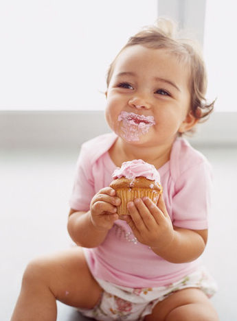 little girl eating a pink cupcake