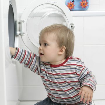 Toddler reaching into washing machine: laundry pod poison risk