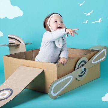 Baby in cardboard airplane