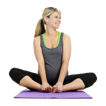 A young pregnant woman sitting on a purple yoga mat