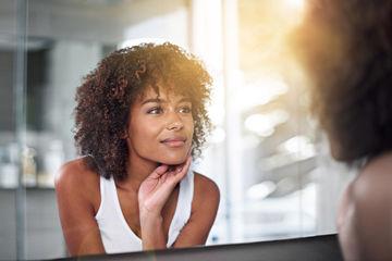 Woman Checks Skin in Mirror