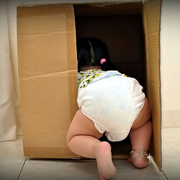 little girl crawling into a cardboard box