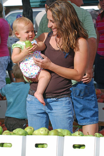 Mother With Baby At Local Farmers Market Holding A Pear
