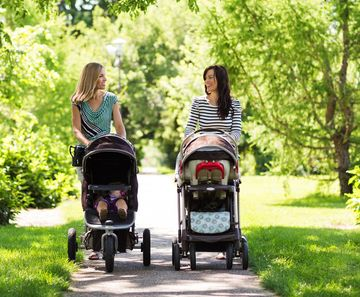 Two Moms Walking Strollers Through Park