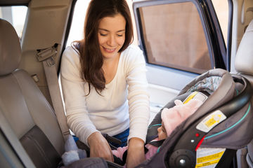Mom Installing Newborn Baby into Car Seat