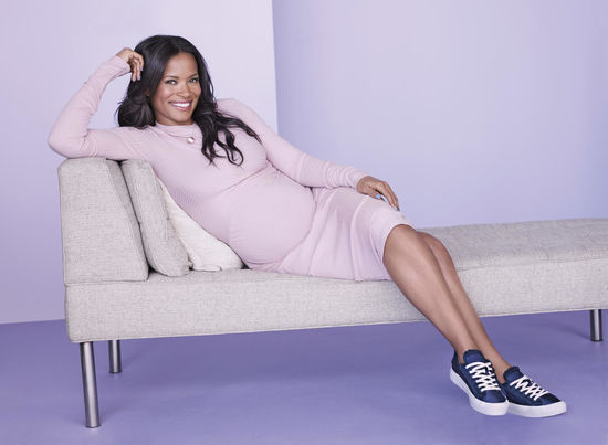Rose Rollins Laying on Couch in Lavender Dress and Navy Sneakers